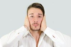Hombre joven triste o irritado que cubre sus oídos con las manos Imagen de archivo