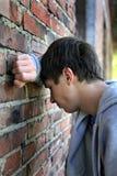 Hombre joven triste por la pared Imagen de archivo libre de regalías