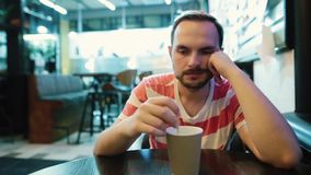 Hombre joven, triste que espera alguien en café en la ciudad almacen de metraje de vídeo