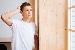 Hombre joven triste que mira hacia fuera la ventana Imagen de archivo