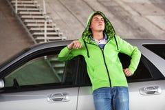 Hombre joven triste que se coloca al lado de su coche al aire libre Fotografía de archivo libre de regalías