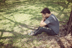 Hombre joven triste que se sienta en el parque Imagenes de archivo