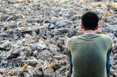 Hombre joven triste que se sienta en la tierra estéril Busque un campo seco del arroz Imagen de archivo libre de regalías