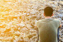 Hombre joven triste que se sienta en la tierra estéril Busque un campo seco del arroz Imágenes de archivo libres de regalías