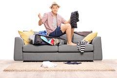 Hombre joven triste que se sienta en su maleta overstuffed Imágenes de archivo libres de regalías