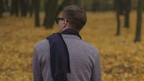 Hombre joven triste que se sienta solamente en parque melancólico del otoño, sintiendo infeliz y solo almacen de video