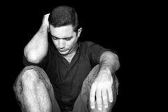 Hombre joven triste y subrayado que se sienta en el piso Foto de archivo libre de regalías