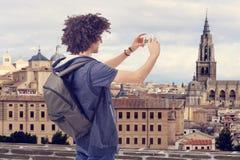 Hombre joven turístico con la mochila que toma la imagen Foto de archivo libre de regalías