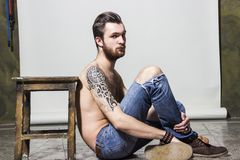 Hombre joven unshaved melenudo entintado atractivo muscular brutal con el tatuaje en su hombro y barba imágenes de archivo libres de regalías