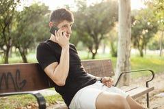 Hombre joven usando el teléfono que se sienta en un banco de parque imagen de archivo