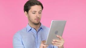 Hombre joven usando la tableta en fondo rosado almacen de metraje de vídeo