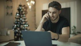 Hombre joven usando lugar de trabajo del teléfono en casa Hombre de negocios feliz que habla el tel?fono m?vil almacen de video