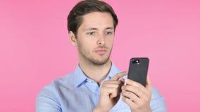 Hombre joven usando Smartphone en fondo rosado almacen de metraje de vídeo