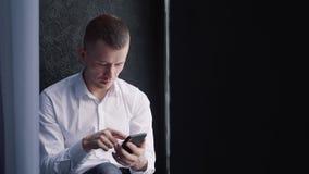 Hombre joven usando su celular elegante moderno almacen de metraje de vídeo