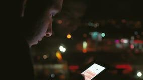Hombre joven usando tecnología elegante del app de la célula del teléfono en la noche delante de luces borrosas de la ciudad almacen de metraje de vídeo