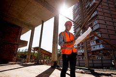 Hombre joven vestido en camisa, chaleco anaranjado del trabajo y casco para explorar la documentación de la construcción en el so fotografía de archivo