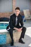 Hombre joven vestido pozo en el borde de la piscina Foto de archivo libre de regalías