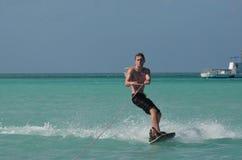 Hombre joven Wakeboarding en aguas calientes tropicales de Aruba fotos de archivo