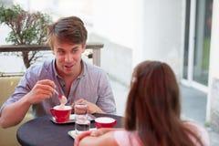 Hombre joven y café de consumición de la mujer al aire libre y que tiene una charla encendido Imagen de archivo