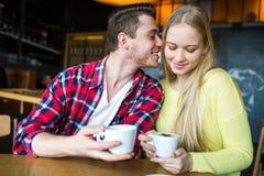 Hombre joven y café de consumición de la mujer en un restaurante Hombre joven y café de consumición de la mujer una fecha Hombre  Fotos de archivo libres de regalías