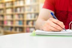 Hombre joven y estudiante atléticos que estudian y que escriben notas fotos de archivo libres de regalías