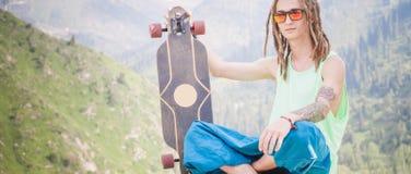 Hombre joven y hermoso del hippie con el monopatín del longboard en la montaña Fotos de archivo libres de regalías