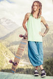 Hombre joven y hermoso del hippie con el monopatín del longboard en la montaña Imagen de archivo