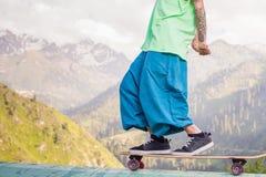 Hombre joven y hermoso del hippie con el monopatín del longboard en la montaña Imágenes de archivo libres de regalías