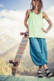 Hombre joven y hermoso del hippie con el monopatín del longboard en la montaña Foto de archivo