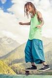 Hombre joven y hermoso del hippie con el monopatín del longboard en la montaña Fotografía de archivo libre de regalías