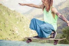 Hombre joven y hermoso del hippie con el monopatín del longboard en la montaña Fotografía de archivo