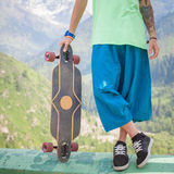 Hombre joven y hermoso del inconformista con el monopatín del longboard en la montaña Foto de archivo
