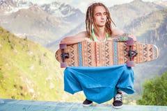Hombre joven y hermoso del inconformista con el monopatín del longboard en la montaña Foto de archivo libre de regalías
