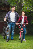 Hombre joven y muchacha adolescente con las bicicletas que se divierten en el parque Fotos de archivo libres de regalías