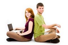 Hombre joven y muchacha con el ordenador portátil Foto de archivo