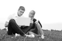 Hombre joven y muchacha con la computadora portátil imagenes de archivo