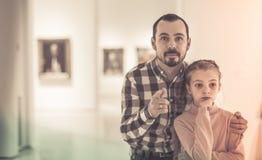 Hombre joven y muchacha que miran pinturas en museo Fotografía de archivo libre de regalías