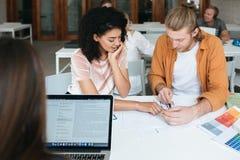 Hombre joven y muchacha que trabajan y que hacen notas juntas en oficina Señora afroamericana hermosa con el pelo rizado oscuro foto de archivo