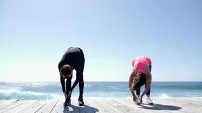 Hombre joven y mujer aptos que hacen estirando excercises en un día soleado en la playa C?mara lenta almacen de metraje de vídeo