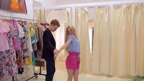 Hombre joven y mujer con la diversión que elige la ropa para ella en el vestuario almacen de metraje de vídeo