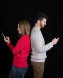 Hombre joven y mujer con los teléfonos móviles Imágenes de archivo libres de regalías