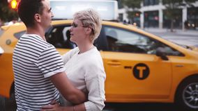 Hombre joven y mujer de la cámara lenta que se unen y que abrazan en la travesía de la calle de Nueva York, taxi amarillo que pas almacen de video