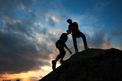 Hombre joven y mujer de los pares que suben en el canto rodado Mano amiga Siluetas en fondo de la puesta del sol fotos de archivo
