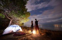 Hombre joven y mujer de los pares que tienen resto en la tienda turística y la hoguera ardiente en orilla de mar cerca de bosque foto de archivo libre de regalías