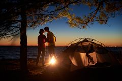 Hombre joven y mujer de los pares que tienen resto en la tienda turística y la hoguera ardiente en orilla de mar cerca de bosque imagen de archivo