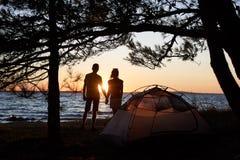 Hombre joven y mujer de los pares que tienen resto en la tienda turística y la hoguera ardiente en orilla de mar cerca de bosque fotos de archivo