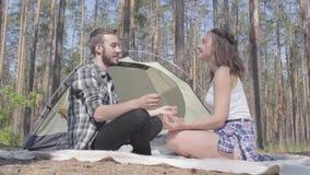 Hombre joven y mujer del retrato que se sientan delante de uno a en meditar del bosque La tienda en el fondo loving almacen de metraje de vídeo
