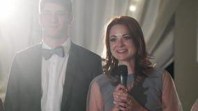 Hombre joven y mujer, el par precioso dice discurso de la tostada en el partido de la celebración - boda, cumpleaños o aniversari metrajes