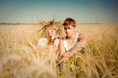 Hombre joven y mujer en campo de trigo Imágenes de archivo libres de regalías