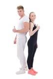 Hombre joven y mujer en los pulgares de la ropa de deportes para arriba aislados en blanco Fotografía de archivo libre de regalías